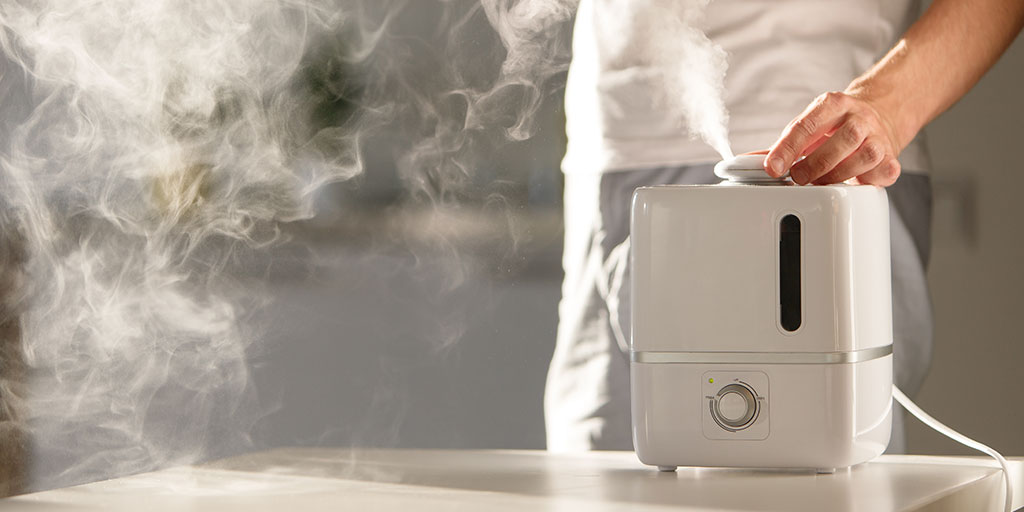 Man turning on a humidifier.